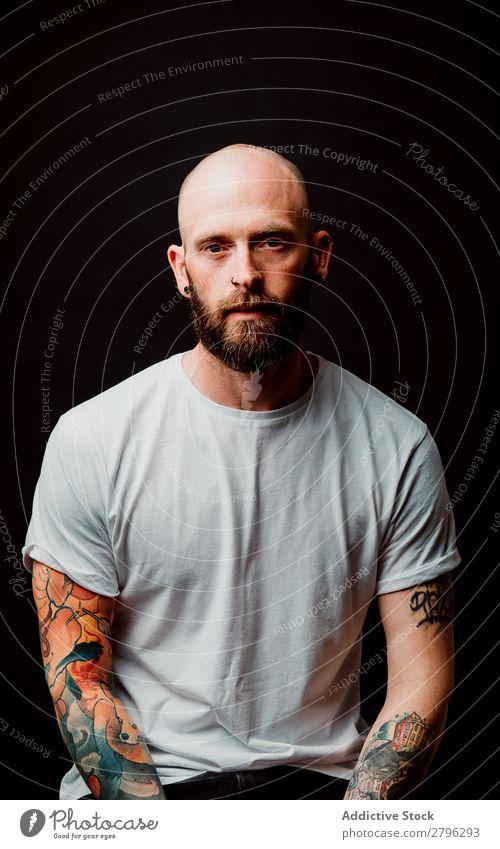 Junger kahlköpfiger Typ mit Tattoos Mann Schickimicki Glatze Jugendliche bärtig T-Shirt Hand haarlos lässig gutaussehend Kunst Coolness Stil trendy