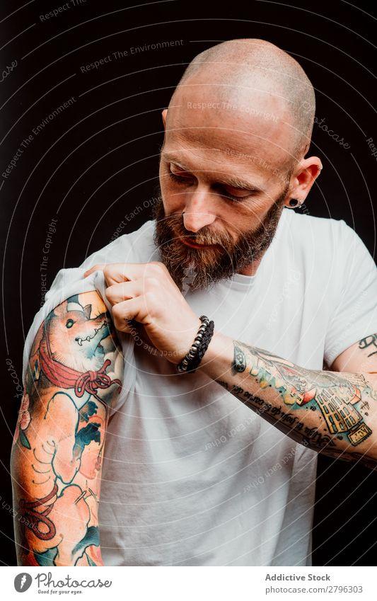 Junger kahlköpfiger Typ mit Tattoos Mann Schickimicki Glatze Jugendliche bärtig T-Shirt Hand haarlos zeigen lässig gutaussehend Kunst Coolness Stil trendy