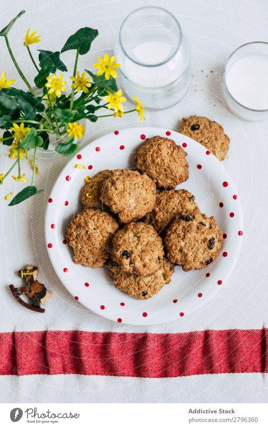 Kekse und Milch in der Nähe von Blumen Plätzchen Vase Tisch Teller Glas Flasche Haferflocken Frühstück Pferd Dekor Snack Dessert süß Lebensmittel gebastelt