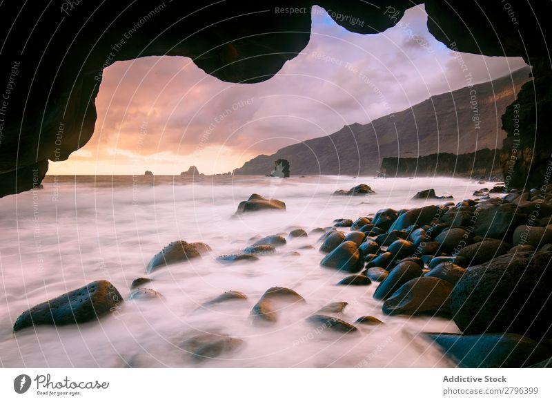 Erstaunliches Steinufer und rosa Himmel mit Wolken Küste Wasser hierro island Kanaren Spanien erstaunlich Meer Oberfläche Sonnenuntergang Felsen malerisch