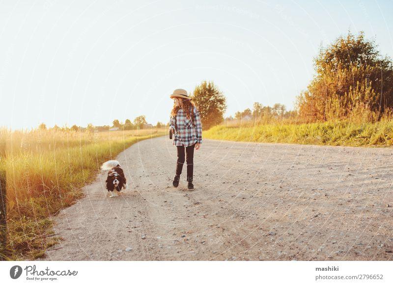 fröhliches Kind Mädchen geht mit ihrem Hund auf der Landstraße spazieren. Lifestyle Freude Freizeit & Hobby Spielen Ferien & Urlaub & Reisen Ausflug Abenteuer