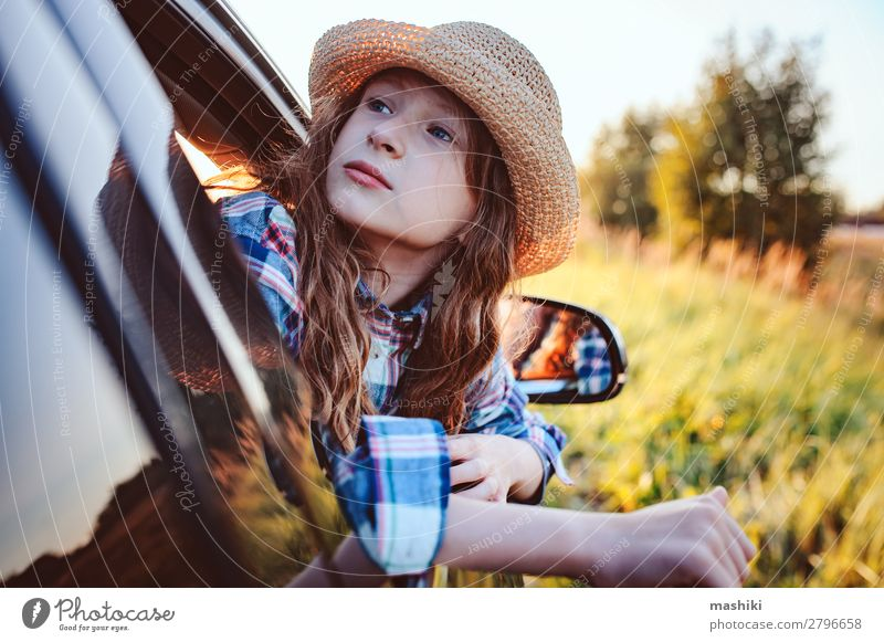 fröhliches Kind Mädchen, das aus dem Autofenster schaut. Lifestyle Freude Freizeit & Hobby Spielen Ferien & Urlaub & Reisen Ausflug Abenteuer Freiheit