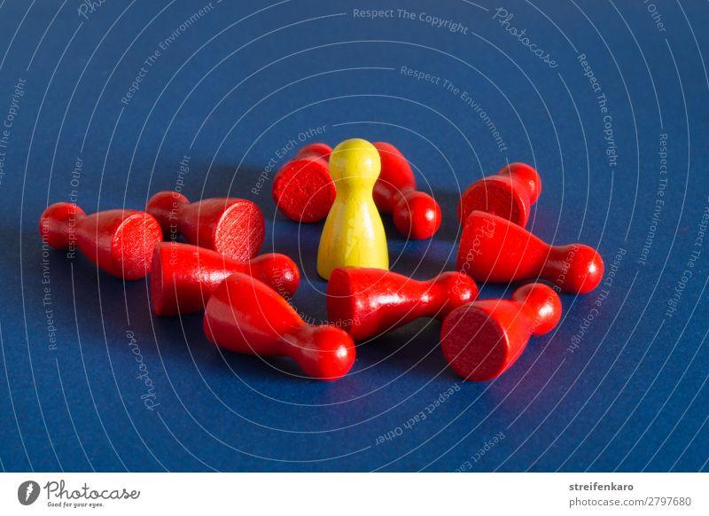 Eine gelbe Spielfigur steht inmitten von vielen roten liegenden Spielfiguren auf blauem Untergrund Wirtschaft Menschengruppe Spielzeug Holz sprechen fallen