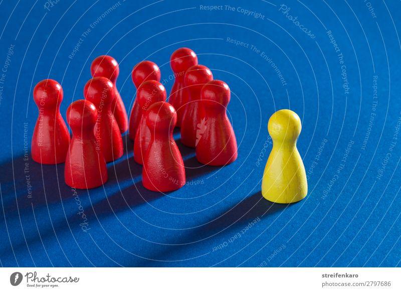 Eine gelbe Spielfigur steht vor einer Gruppe von roten Spielfiguren auf blauem Untergrund lernen Wirtschaft Business Karriere Erfolg sprechen Team