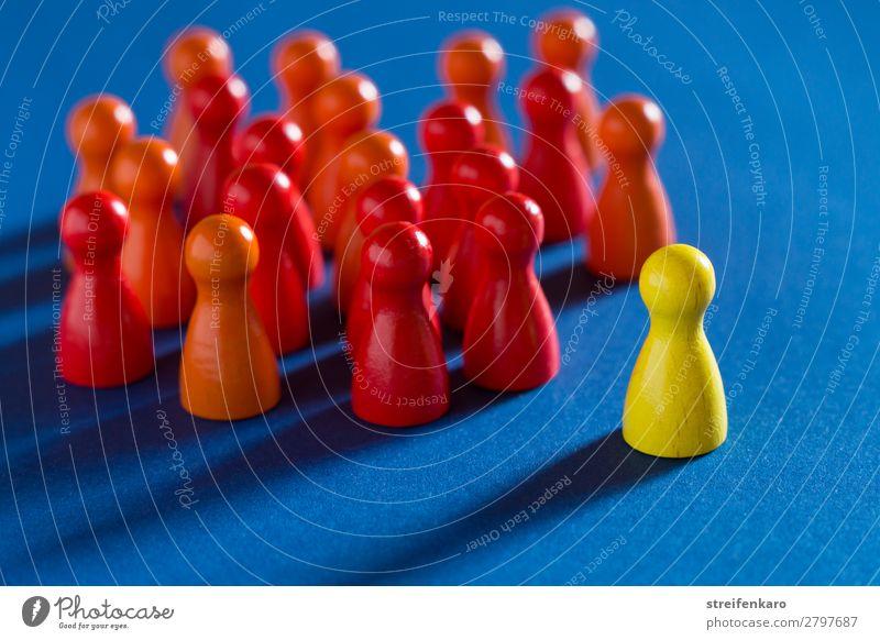Eine einzelne gelbe Spielfigur steht gegenüber einer Gruppe von roten Spielfiguren auf blauem Untergrund lernen Berufsausbildung Wirtschaft Business Karriere