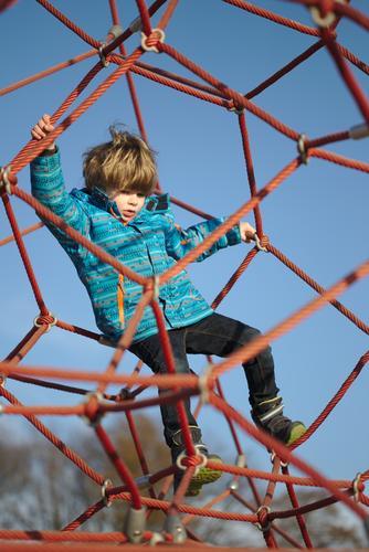 Kind Klettert auf dem Spielplatz Mensch Junge Kindheit 1 3-8 Jahre Umwelt Natur Himmel Wolkenloser Himmel Winter Bewegung festhalten Spielen authentisch