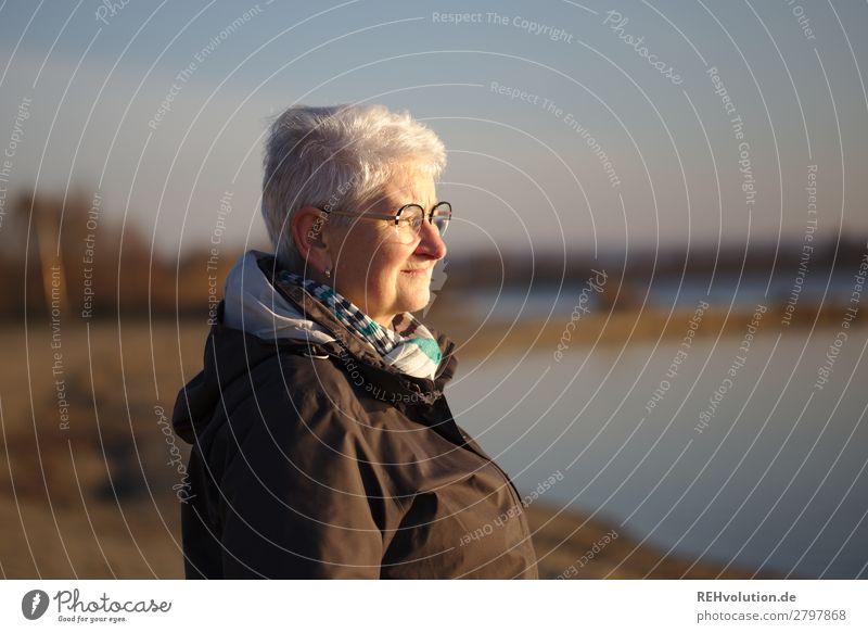 Seniorin mit Ausblick am See grauhaarig alt friedlich Außenaufnahme Landschaft Sonnenlicht Idylle Schönes Wetter Himmel stille ruhig Mensch Abendlicht kritisch