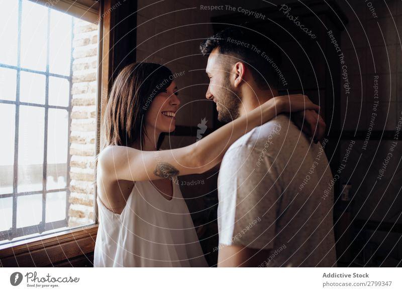 Ein glückliches Paar, das sich in der Küche umarmt. umarmend Lächeln Fenster heimwärts Mann Frau Liebe Partnerschaft Zusammensein Lifestyle romantisch Stil