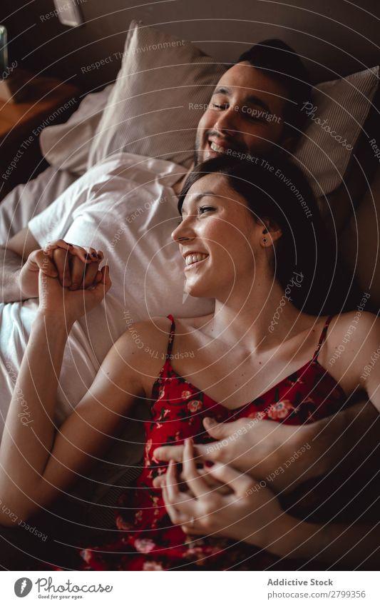 Ein glückliches Paar kuschelt auf dem Bett. umarmend Lächeln heimwärts Mann Frau Liebe Kuscheln Schlafzimmer Partnerschaft Zusammensein Lifestyle romantisch