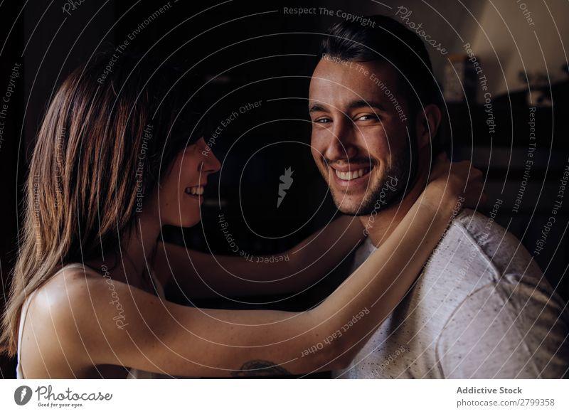 Glückliches Paar sitzt auf dem Bett umarmend Lächeln heimwärts Mann Frau Liebe Kuscheln Schlafzimmer Partnerschaft Zusammensein Lifestyle romantisch Stil