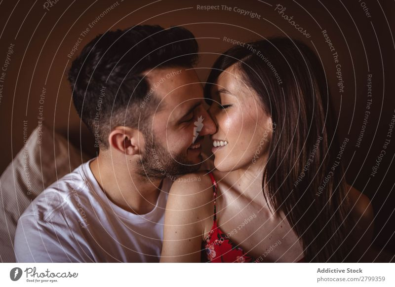 Glückliches Paar sitzt auf dem Bett umarmend Lächeln heimwärts Mann Frau Liebe Schlafzimmer Partnerschaft Zusammensein Lifestyle romantisch Stil gemütlich