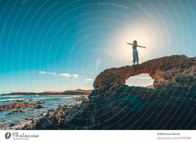Anonyme Frau mit ausgestreckten Armen auf einer Klippe in Meeresnähe. ausgestreckte Arme Freiheit Lifestyle Freizeit & Hobby ruhen Erholung Wellen Küste