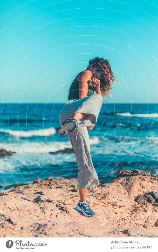 Anonyme Frau, die Luft an der Küste tritt. tretend Meer Himmel blau Schönes Wetter Lifestyle Freizeit & Hobby Wellen Stein Wasser Bewegung üben Gleichgewicht