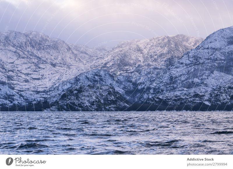 Ufer mit Bergen am Wasser Küste Berge u. Gebirge Felsen Klippe Stein Himmel Wolken Oberfläche winkend erstaunlich weiß natürlich Aussicht Hügel Landen