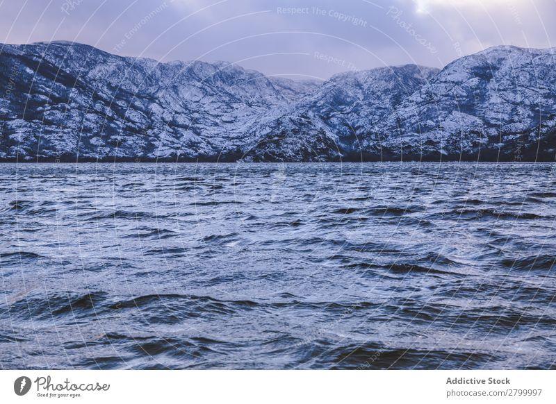 Ufer mit Bergen am Wasser Küste Schnee Berge u. Gebirge Felsen Klippe Stein Himmel Wolken Oberfläche winkend erstaunlich weiß natürlich Aussicht Hügel Landen