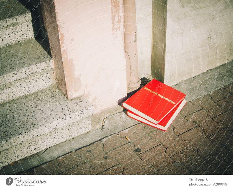 Enzyklopädie der Straße Stadt rot Lexikon Straßenbelag Buch Treppenabsatz Haus Wand Müll entsorgen Pflastersteine Wissen klug Bildung lernen lesen Außenaufnahme