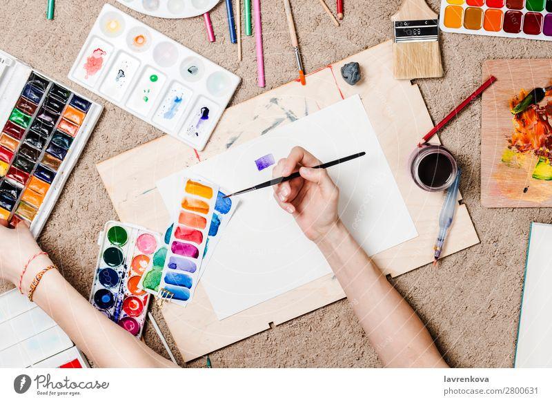 Flachlegen mit Frauenhänden, die stationäre Vorräte halten. Künstler Holzplatte Kaktus Teppich Kaukasier Farbe mehrfarbig Handwerk Kreativität Designer zeichnen