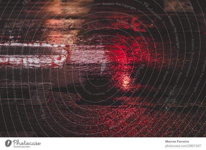 nasser Asphalt mit Rotlichtreflexion Urelemente schlechtes Wetter Regen Stadt Straße Straßenkreuzung Ampel Wasser kalt Farbfoto Außenaufnahme Menschenleer Nacht