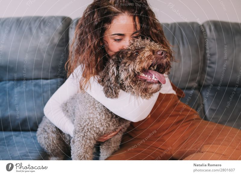 Ein hübsches Mädchen umarmt ihr Haustier, während es sie küsst. Lifestyle Freude schön Erholung Freizeit & Hobby Raum Wohnzimmer Schlafzimmer Mensch feminin