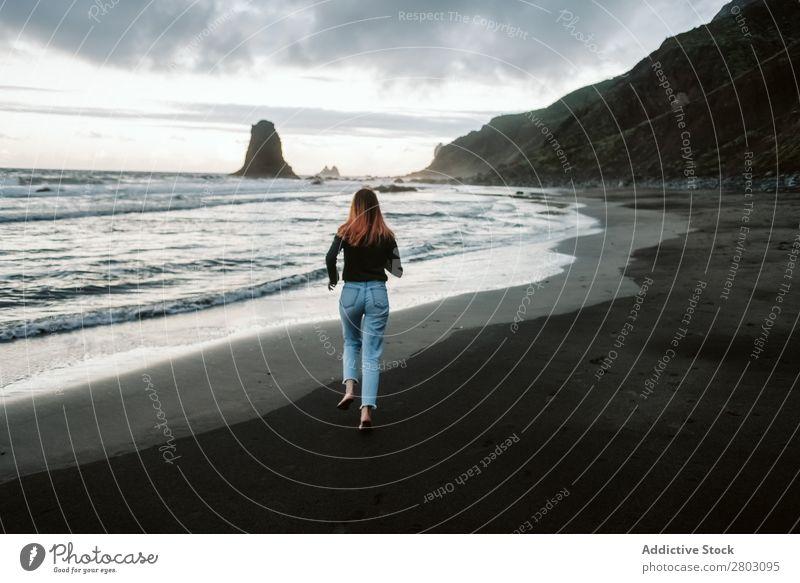 Barfuß-Frau, die in der Nähe des wogenden Meeres läuft. rennen Küste Unwetter Wellen Wolken Himmel Ferien & Urlaub & Reisen lässig Stil trendy Tourismus Ausflug