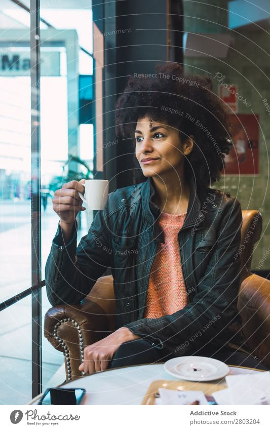 Schwarze Frau mit Afrohaar, die einen Kaffee trinkt. Afrikanisch Afro-Look Amerikaner attraktiv schön Beautyfotografie schwarz lässig Tasse trinken Mode Mädchen