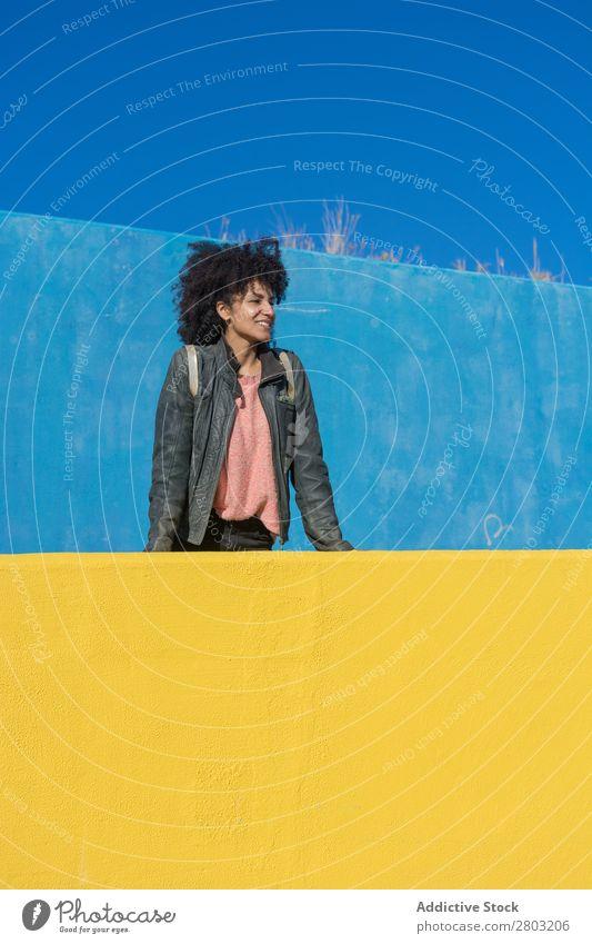 Schwarze Frau mit Afrohaar, die sich an bunte Wände lehnt. Erwachsene Afrikanisch Afro-Look Amerikaner Hintergrundbild schön Beautyfotografie schwarz blau