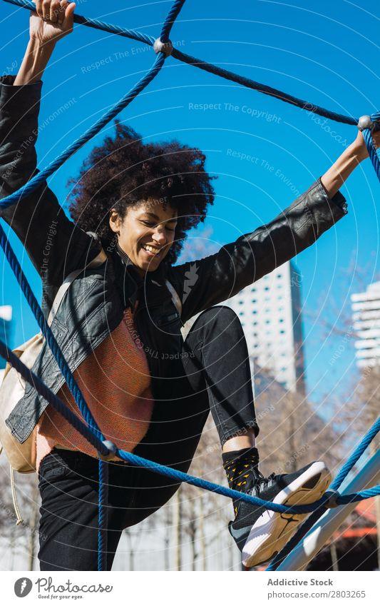 Frau mit Afrohaar klettert bei Kinderattraktionen. Aktion Afrikanisch Afro-Look schwarz heiter Kindheit Klettern niedlich Gerät Familie & Verwandtschaft Freude