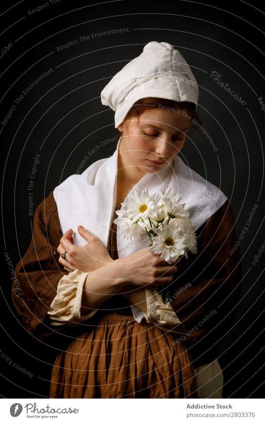 Mittelalterliches Dienstmädchen mit Blumen mittelalterlich rothaarig Frau Halt Margeriten Bekleidung historisch Kleid Kostüm Jungfer Motorhaube Renaissance