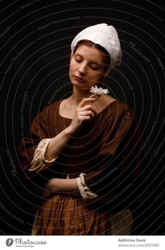 Mittelalterliches Dienstmädchen mit Blume mittelalterlich rothaarig Frau Halt Gänseblümchen Bekleidung historisch Kleid Kostüm Jungfer Motorhaube Renaissance