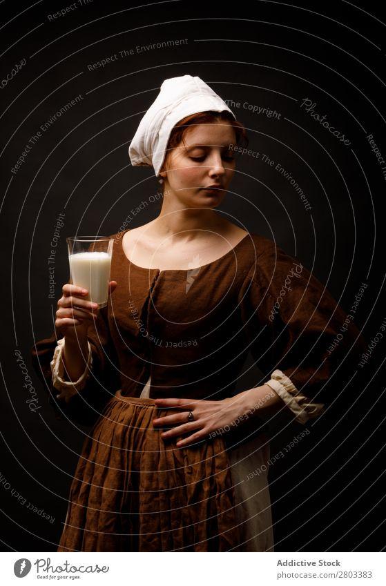 Mittelalterliches Dienstmädchen mit einem Glas Milch mittelalterlich rothaarig Frau geschlossene Augen Bekleidung historisch Kleid Kostüm Jungfer Motorhaube