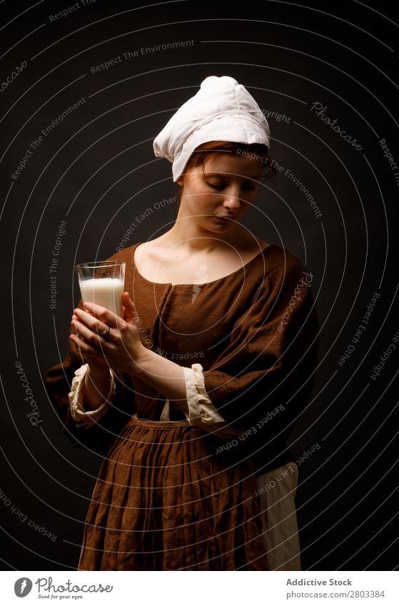 Mittelalterliches Dienstmädchen mit einem Glas Milch mittelalterlich Frau geschlossene Augen Bekleidung historisch Kleid Kostüm Jungfer Motorhaube Renaissance