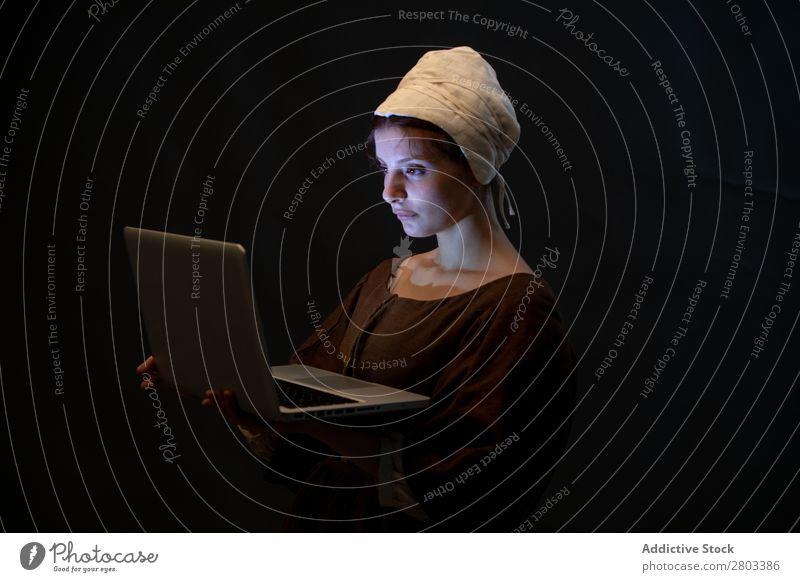 Mittelalterliches Dienstmädchen mit Laptop mittelalterlich Notebook benutzend Entwurf Frau geschlossene Augen Bekleidung historisch Kleid Kostüm Jungfer