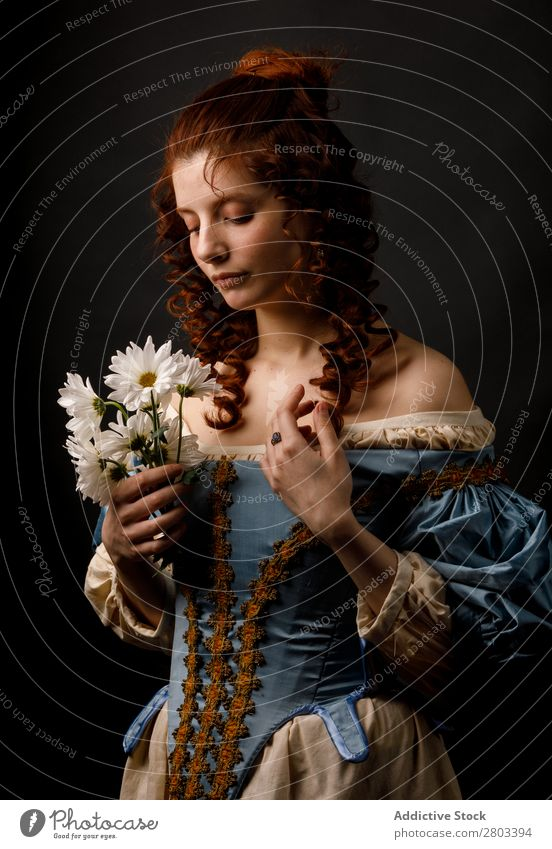 Barocke Frau mit geschlossenen Augen, die Blumen hält. Margeriten rothaarig Korkenzieher geschlossene Augen Kleid mittelalterlich Karneval Renaissance