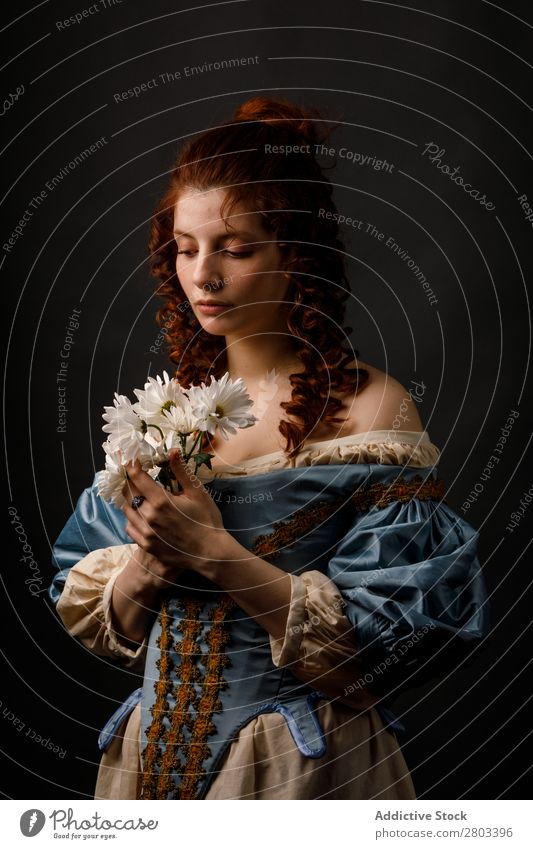 Barocke Frau mit geschlossenen Augen, die Blumen hält. rothaarig Korkenzieher Kleid mittelalterlich Karneval Renaissance Prinzessin Königlich Maskerade genießen