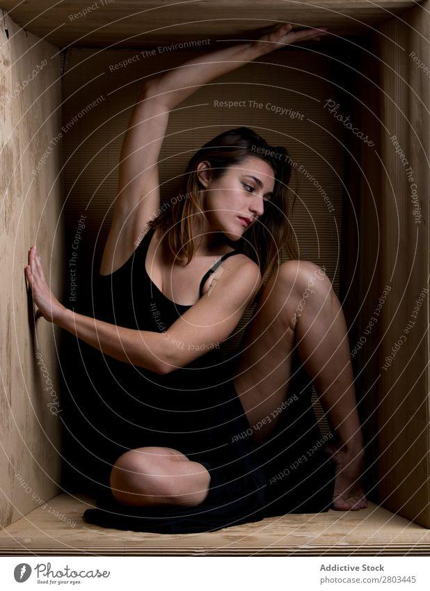 Provokante Frau im Karton sitzend verführerisch Kleid Kasten Bildunterschrift aufreizend Entwurf Körperhaltung reizvoll genießen attraktiv Model eingeschränkt