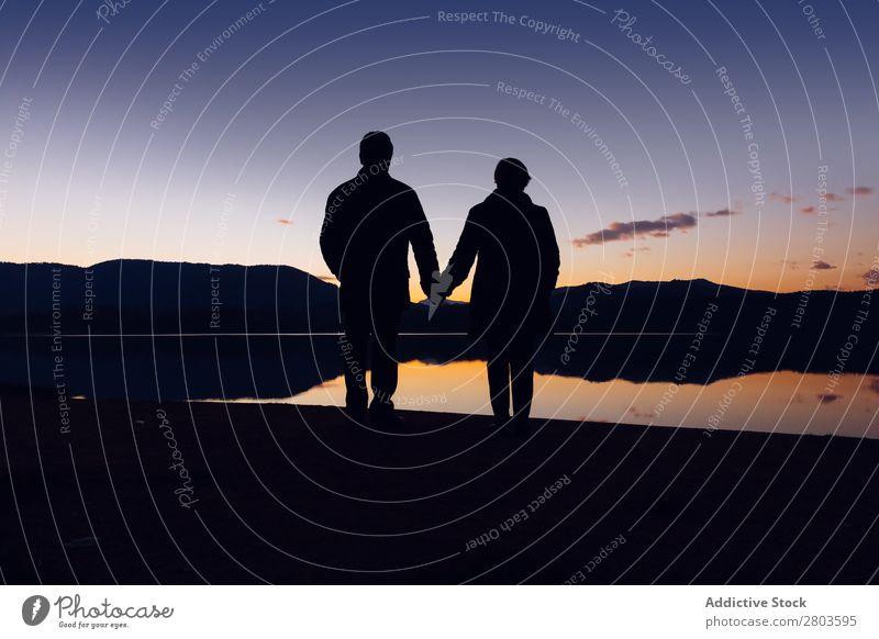 Anonymes Paar, das während des Sonnenuntergangs am Wasser steht. Küste Händchenhalten romantisch Abend Zusammensein Liebe Silhouette Ferien & Urlaub & Reisen