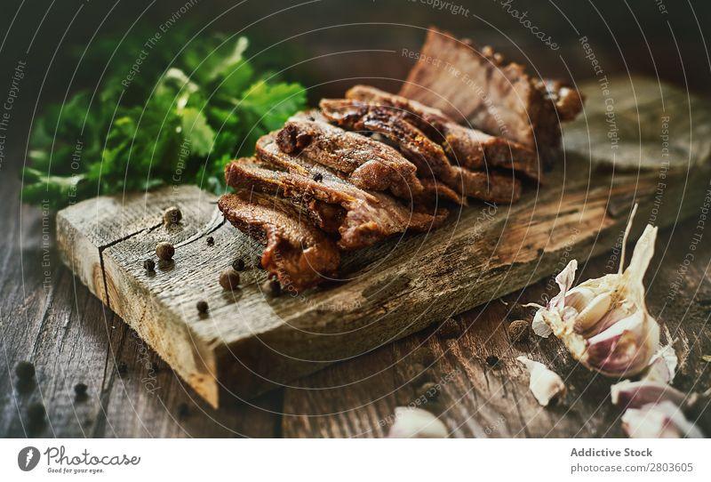 Gewürze in der Nähe von leckerem gebratenem Fleisch Schinken Knoblauch Petersilie Tisch Holzplatte Kräuter & Gewürze Lebensmittel Scheiben Abendessen frisch