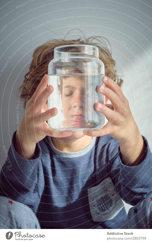 Junge hält Vase mit Wasser in der Nähe des Gesichts. Sauberkeit durchsichtig heimwärts Wand weiß lässig Kind Reinheit anschaulich frisch Freude niedlich