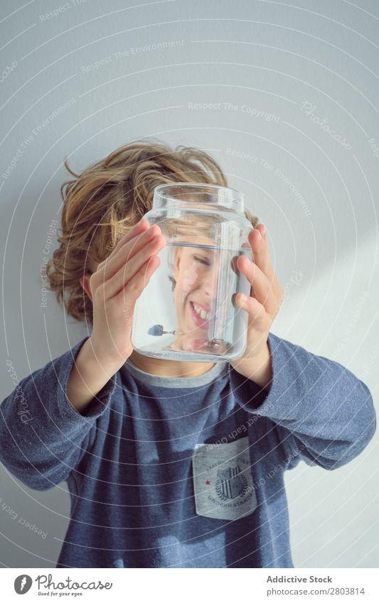 Junge hält Vase mit Wasser in der Nähe des Gesichts. Sauberkeit durchsichtig heimwärts Wand weiß lässig Kind Reinheit anschaulich frisch heiter Freude Glück