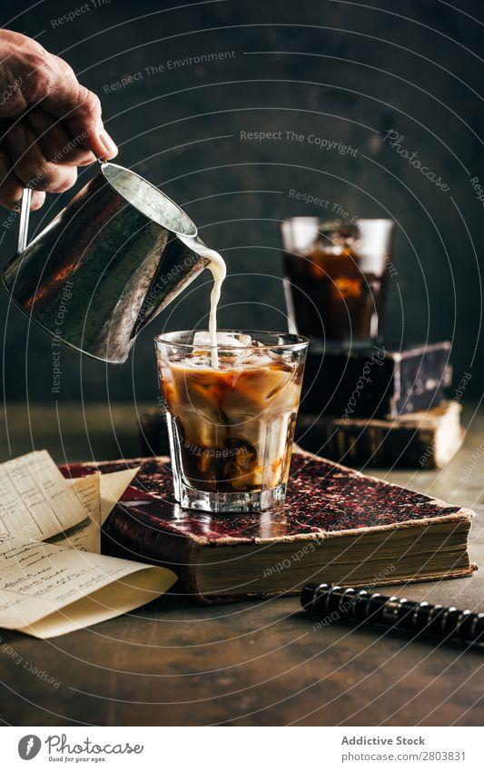 Gießen von Milch in ein kaltes Espressoglas Antiquität aromatisch Bohnen Getränk Buch Frühstück brauen braun Koffein Kaffee Kaffeepause Kaffeekanne Creme Tasse