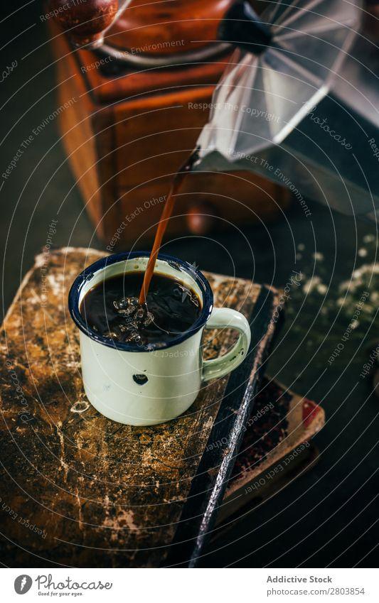 Portionieren von heißem Kaffee in einer Email-Tasse Antiquität aromatisch Bohnen Getränk schwarz Buch Frühstück Koffein Kaffeepause Kaffeekanne Creme trinken