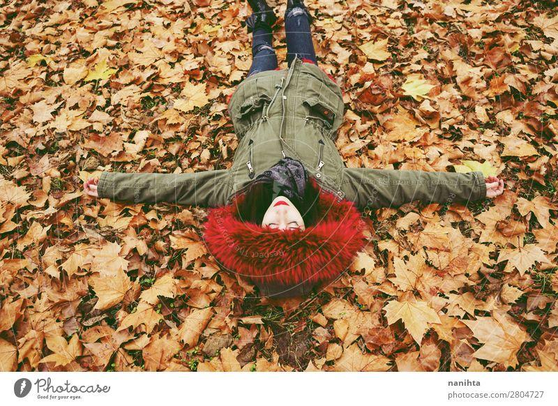 Junge Frau, die auf dem Boden voller Herbstblätter liegt. Lifestyle Stil Gesicht Gesundheit Wellness Wohlgefühl Erholung ruhig Freizeit & Hobby Mensch feminin
