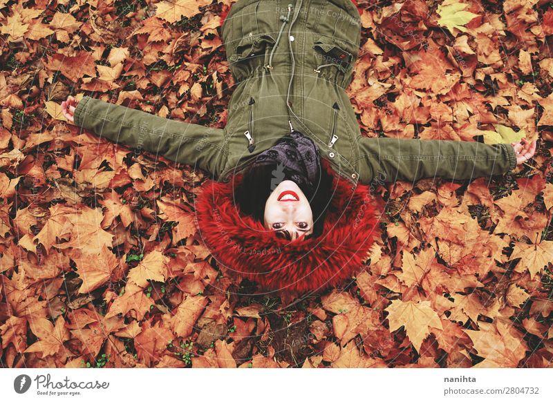 Junge Frau, die auf dem Boden voller Herbstblätter liegt. Gesicht ruhig Freizeit & Hobby Mensch feminin Erwachsene Jugendliche 1 18-30 Jahre Umwelt Natur Blatt