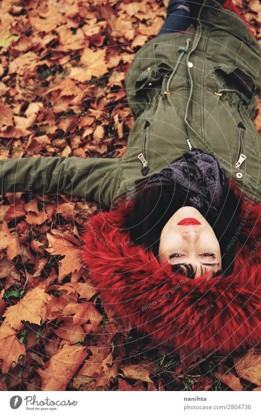 Junge Frau, die auf dem Boden voller Herbstblätter liegt. Lifestyle Stil Gesicht ruhig Freizeit & Hobby Mensch feminin Erwachsene Jugendliche 1 18-30 Jahre