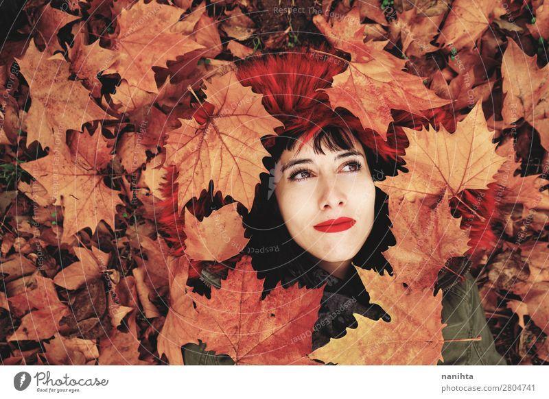 Junge Frau, die auf dem Boden voller Herbstblätter liegt. Lifestyle Stil Freude schön Gesicht Wellness Wohlgefühl ruhig Freizeit & Hobby Mensch feminin