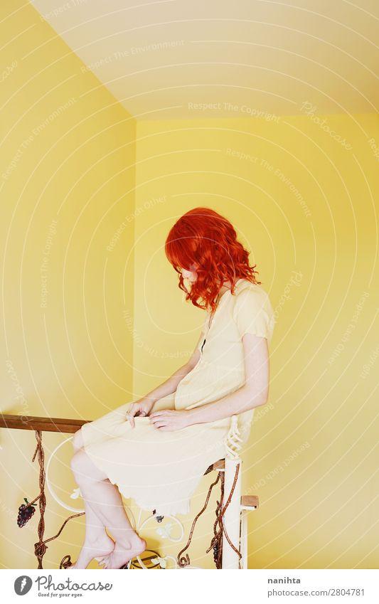 Junge rothaarige Frau mit einem gelben Kleid in einem gelben Raum. Lifestyle Stil schön Haare & Frisuren ruhig Mensch feminin Junge Frau Jugendliche Erwachsene