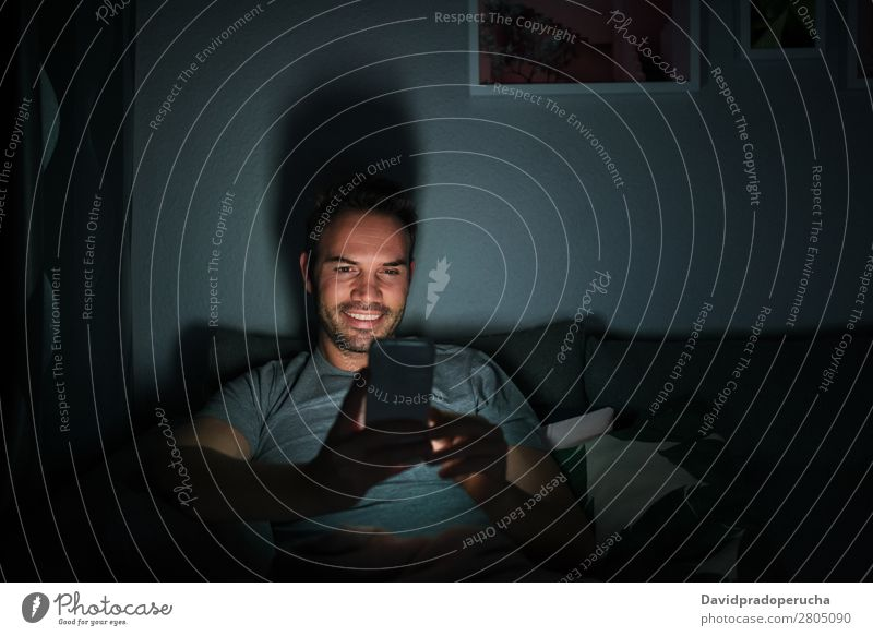 Mann im Pyjama mit Handy Erwachsene attraktiv schön Junge Kaukasier bequem Mitteilung Textfreiraum Liege gemütlich dunkel Gerät gutaussehend Glück heimwärts