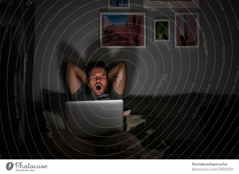 Mann im Pyjama mit gähnendem Computer Erwachsene attraktiv schön Junge Kaukasier bequem Mitteilung Textfreiraum Liege gemütlich dunkel Gerät Abend gutaussehend