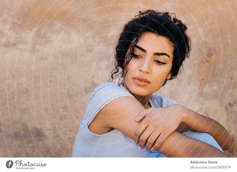 Schöne ethnische Frau in der Nähe einer schäbigen Mauer. Marokkaner Wand urwüchsig elegant anlehnen Außenseite Gebäude Jugendliche Model dünn dreckig genießen