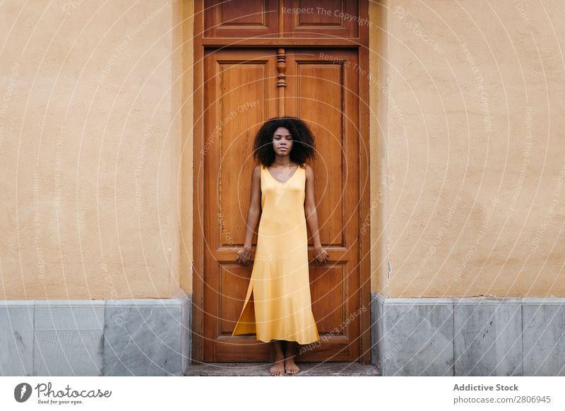 Wunderschöne schwarze Frau in Kleid auf der Straße. Tür lockig Stadt genießen Barfuß traumhaft urwüchsig Afroamerikaner Afro-Look Angebot Körper selbstbewußt